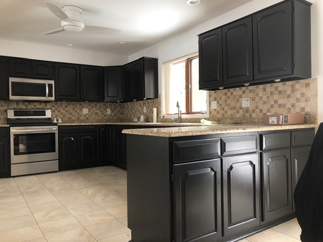 professionally painted kitchen cabinets that are black